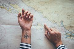 Koordinaten-Tattoo: Frauenhand zeigt mit dem Finger auf eine Weltkarte, ihre andere Hand zeigt nach oben