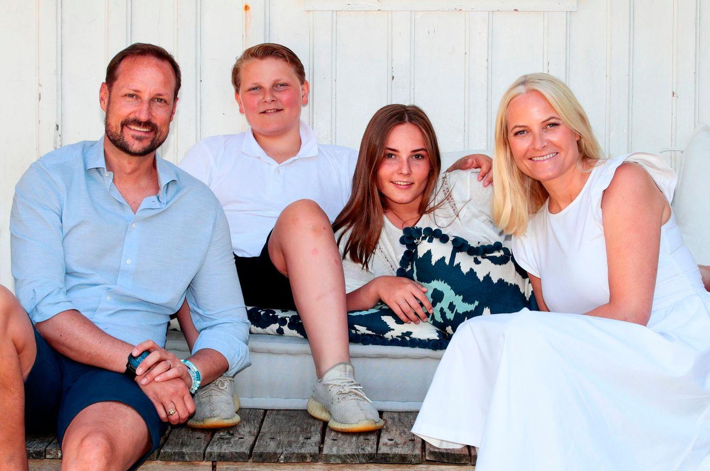 Mette-Marit und Prinz Haakon sitzen mit ihren Kindern vor einem Haus
