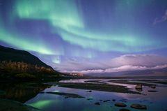 Polarlichter: See und Berge im Himmel grüne und lilafarbene Polarlichter