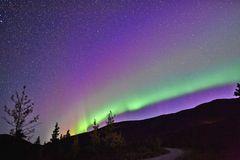 Polarlichter: Nachthimmel mit grünen und lilafarbenen Polarlichtern über einem Hüel