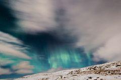 Polarlichter: Schneebedeckter Berg, im Himmel grüne Polarlichter