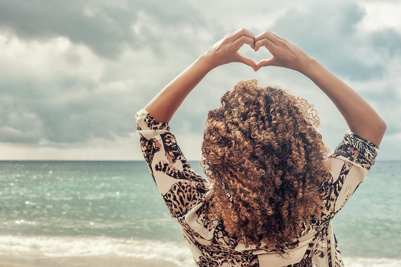 Welches Sternzeichen passt zu Löwe? Eine Frau am Strand hält ein Herz in die Luft