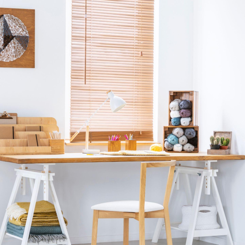 Nähzimmer einrichten: Stuhl und Tisch, mit Wolle in Kisten darauf