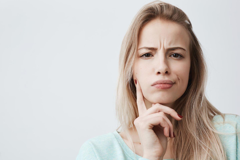 Hohe Stirn: Frau mit hoher Stirn und grübelndem Gesicht