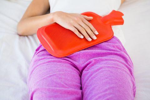 Schmerzen linker Unterbauch: Frau mit Wärmflasche