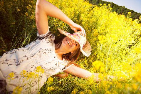 Erdzeichen: Eine Frau mit Hut liegt auf einer gelben Blumenwiese