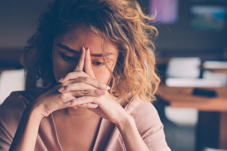Womit macht man sich das Leben unnötig schwer? Eine bedrückte junge Frau starrt vor sich hin