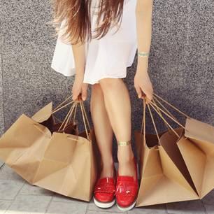 Nachhaltig angezogen: 7 Fakten zu ökologischer Mode: Frau mit vier Papier-Shoppingtüten