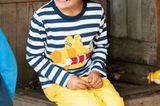 Kindermode: Junge in gelber Hose sitzt auf Kiste