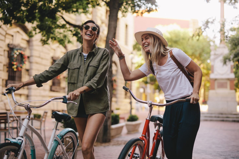 Was kann man machen? 2 Freundinnen schieben ihre Fahrräder und lachen