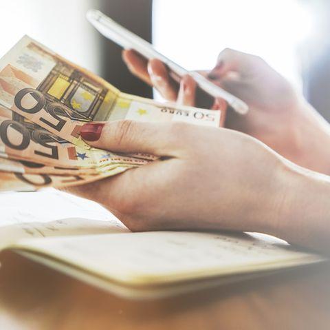 Geldfragen, die wir uns stellen: Frau hält 50-Euro-Scheine in der Hand