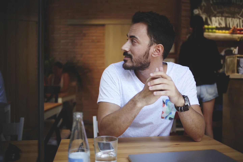 Was stört Männer an perfekten Frauen? Ein Mann sitzt allein an einem Tisch und schaut zur Seite