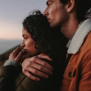 Macht die Beziehung noch einen Sinn? Ein Mann hält seine Freundin von hinten im Arm