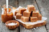 Salty Bar: Salz-Karamell-Pralinen auf einem Holzbrett, daneben eine Schale mit Salz und ein Topf mit Karamell
