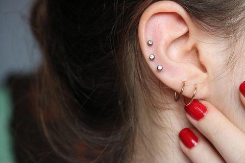 Druck auf den Ohren: Frau fasst sich ans Ohr