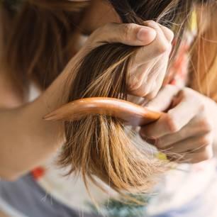 Strohige Haare pflegen: Frau kämmt ihre Haarspitzen