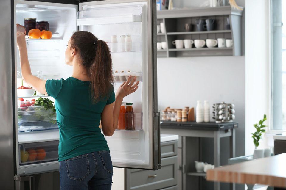 Kühlschrank richtig einräumen: Frau sortiert Kühlschrank ein