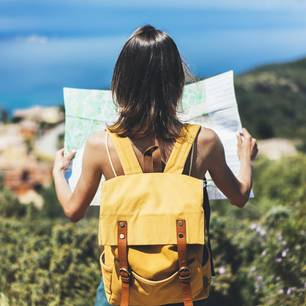 Nachhaltiger Tourismus: Frau mit Rucksack und Karte