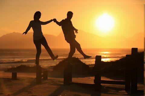 Welches Sternzeichen passt zu Waage? Zwei Menschen balancieren über Balken am Strand