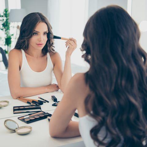 Highlighter auftragen: Frau guckt in den Spiegel und schminkt sich