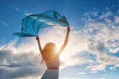 Luftzeichen: Eine Frau hält ein Tuch in die Luft