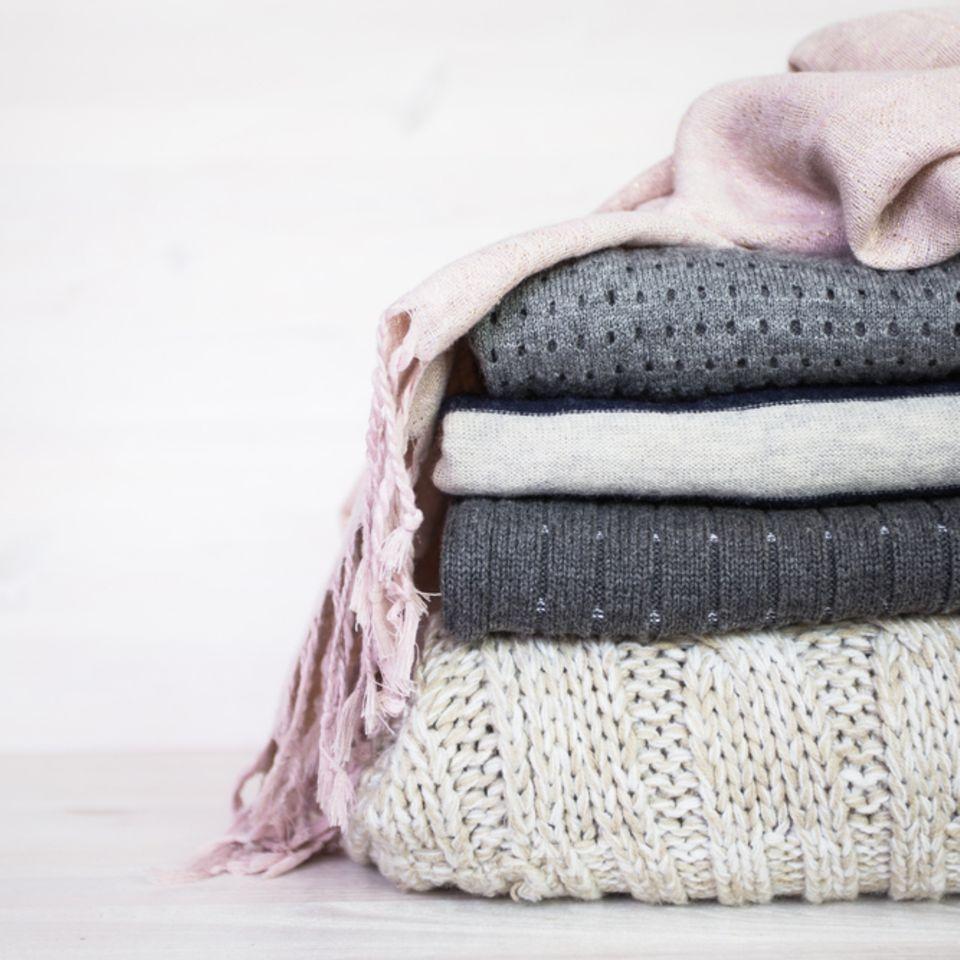 Fusseln entfernen: Wollkleidung liegt zusammengelegt aufeinander