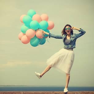 Horoskop: Eine gute gelaunte Frau mit Luftballons