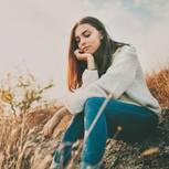 Welche Probleme haben gute Menschen? Eine nachdenkliche junge Frau sitzt auf einer Wiese
