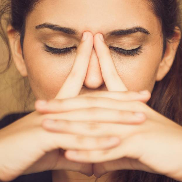 Nasenbluten stoppen: Frau fasst sich an die Nase