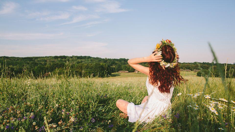 Blumenkranz selber machen: Frau sitzt auf einer Wiese und trägt einen Blumenkranz