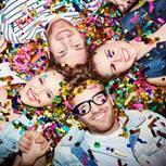 Partyspiele: 4 Freunde liegen auf dem Boden nebeneinander mit Konfetti übersät