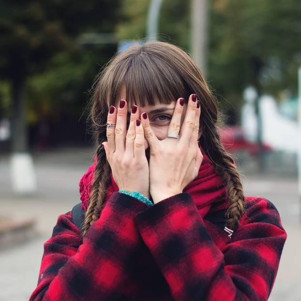 Horoskop: Eine Frau guckt durch ihre Finger