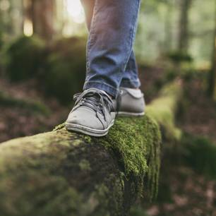 Trick gegen Burnout: Frau balanciert auf einem Baumstamm