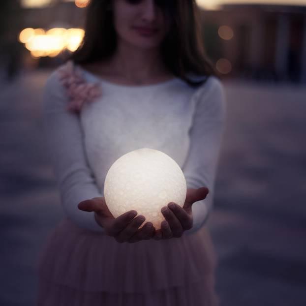 Horoskop: Eine Frau hält einen Vollmond in den Händen