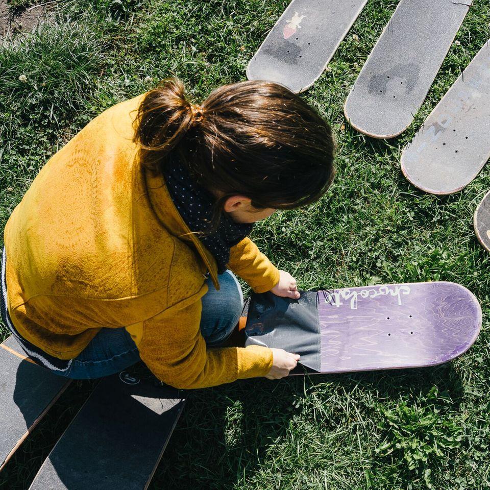 Anna löst das Griptape vom Skateboard