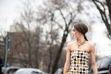 Herbst-Frisuren: Frau steht seitlich auf einer Strasse