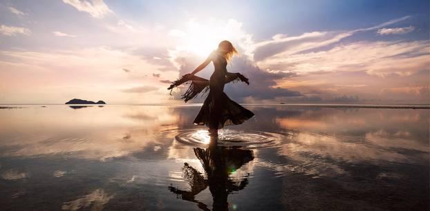 Wasserzeichen: Eine Frau tanzt im flachen Wasser