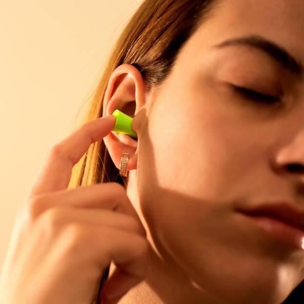 Tinnitus-Behandlung: Frau nutzt Ohrstöpsel