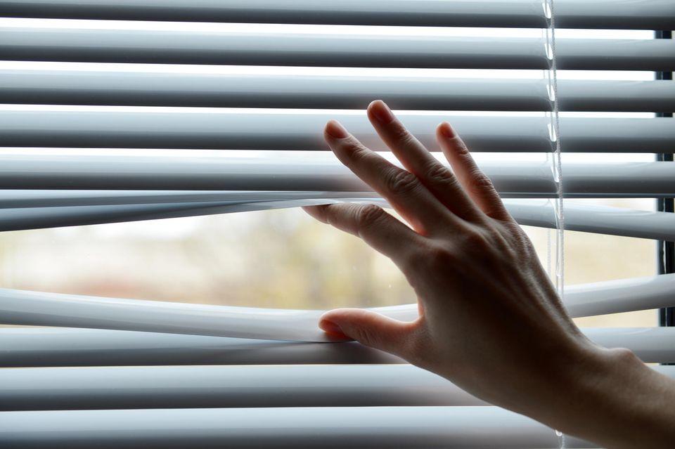 Fenster verdunkeln: Frau schiebt Jalousien nach oben