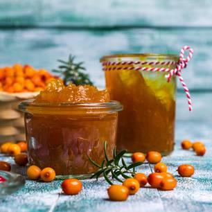 Sanddornmarmelade: Marmelade im Glas und Sanddornbeeren auf dem Boden