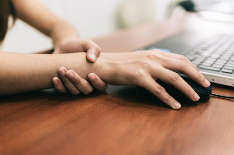 Hausmittel bei Sehnenscheidenentzündung: Person fasst sich am PC ans Handgelenk