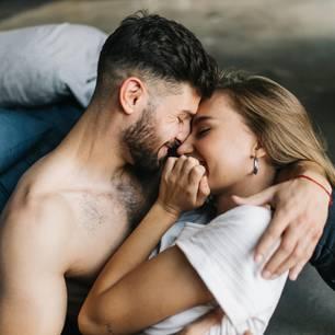 Horoskop: Ein verliebtes Pärchen neben dem Bett
