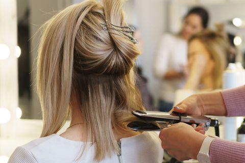 Guten Friseur finden: Frau stylt Haare mit Glätteisen