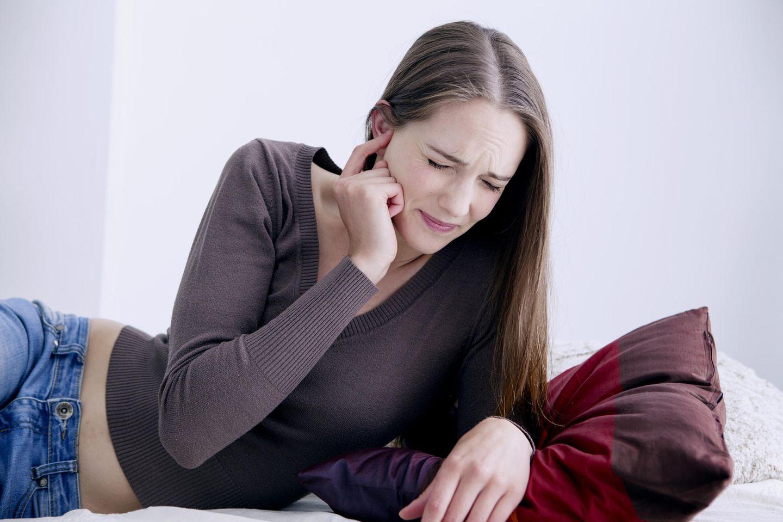 Rauschen im Ohr: Frau hält sich das Ohr