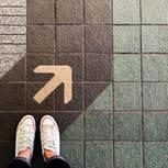 Wie treffe ich die richtige Entscheidung? Eine Frau steht vor einem Pfeil