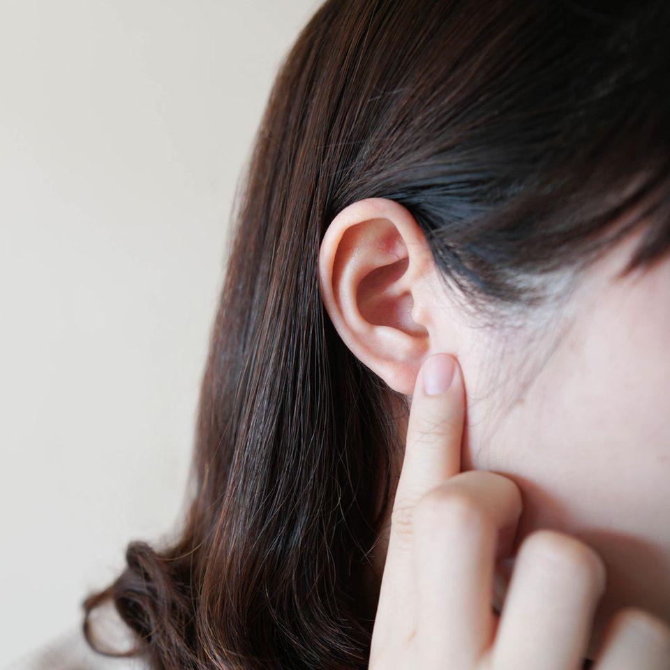 Hörsturz-Symptome: Frau fasst sich ans Ohr