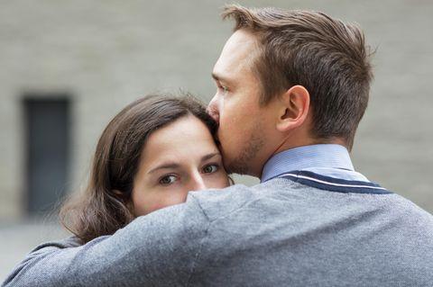 Was muss man dem Partner nicht sagen? Ein Mann nimmt seine schuldig blickende Frau in den Arm