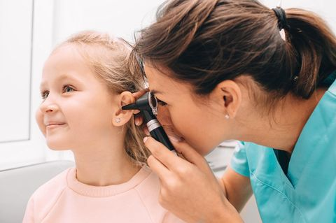 Mittelohrentzündung beim Kind: Ärztin untersucht Mädchen am Ohr