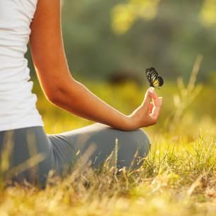 Studie: Eine Frau macht Yoga mit einem Schmetterling