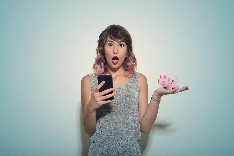 Aktien und ETFs: Frau mit Handy und Sparschwein